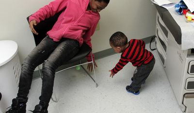 FOR RELEASE SUNDAY, FEBRUARY 23, 2014, AT 12:01 A.M. EST - In this Feb. 4, 2014 photo, Jessica Vick, left, plays with her son, Jasiah Macon, before a visit with Dr. Guillermo Hidalgo, in Greenville, N.C. In December, Jasiah received his mother's kidney on Dec. 20, becoming the youngest kidney transplant patient at Vidant Medical Center. (AP Photo/The Wilson Times, Gray Whitley)