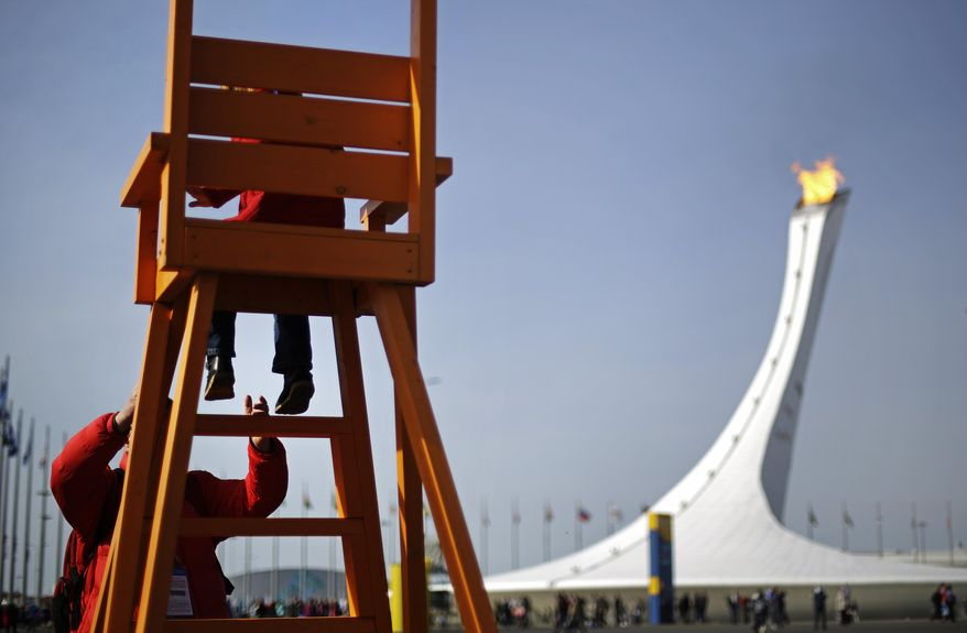 Anton Kirpichenkov helps his daughter, Polina, 4, both of Moscow, down from a large chair overlooking the Olympic cauldron at the 2014 Winter Olympics, Thursday, Feb. 20, 2014, in Sochi, Russia. (AP Photo/David Goldman)