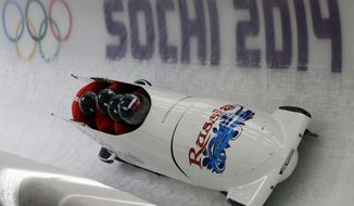 The team from Russia RUS-1, piloted by Alexander Zubkov, take a curve during the men's four-man bobsled training at the 2014 Winter Olympics, Thursday, Feb. 20, 2014, in Krasnaya Polyana, Russia. (AP Photo/Dita Alangkara)