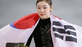 Yuna Kim of South Korea celebrates her second place with the national flag following the flower ceremony for the women's free skate figure skating finals at the Iceberg Skating Palace during the 2014 Winter Olympics, Thursday, Feb. 20, 2014, in Sochi, Russia. (AP Photo/Vadim Ghirda)