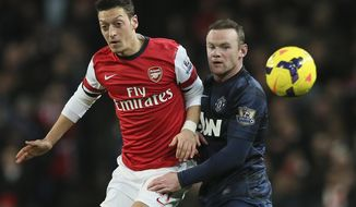 FILE - In this Feb. 12, 2014, file photo, Arsenal's Mesut Ozil, left, nudges the ball from Manchester United's Wayne Rooney during their English Premier League soccer match in London. Less than a year after pushing to leave Manchester United, Rooney committed his long-term future to the struggling Premier League champion on Friday, Feb. 21, by signing a lucrative contract through June 2019. (AP Photo/Alastair Grant, File)
