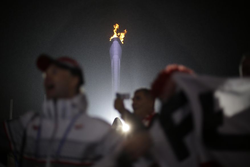 Fans cheer near the Olympic flame while watching the medals ceremonies at the 2014 Winter Olympics, Sunday, Feb. 16, 2014, in Sochi, Russia. (AP Photo/David Goldman)