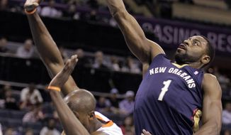 New Orleans Pelicans' Tyreke Evans (1) stretches over Charlotte Bobcats' Anthony Tolliver to score during the first half of an NBA basketball game in Charlotte, N.C., Friday, Feb. 21, 2014. (AP Photo/Bob Leverone)