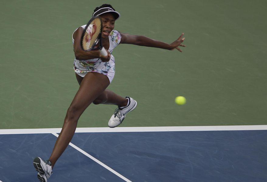 Venus Williams of the U.S. returns the ball to Caroline Wozniacki of Denmark during a semi final match of Dubai Duty Free Tennis Championships in Dubai, United Arab Emirates, Friday, Feb. 21, 2014. (AP Photo/Kamran Jebreili)