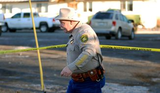 Modoc County Sheriff and Coroner Mike Poindexter ducks under crime scene tape Friday, Feb. 21, 2014 outside the tribal headquarters of the Cedarville Rancheria in Alturas, Calif., where local media reports quote police saying a former tribal leader allegedly killed four people and wounded two others in a gun and knife attack Thursday during an evictiion hearing. (AP Photo/Jeff Barnard)