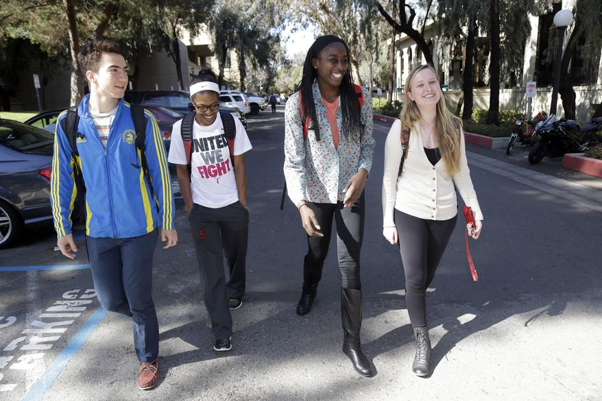 ADVANCE FOR WEEKEND EDITIONS, FEB. 22-23 - In this Feb. 19, 2014 photo, Chiney Ogwumike, a member of Stanford's NCAA college basketball team, center right, walks the university's campus with fellow students Sebastian Le Bras, left, teammate Briana Roberson, and Kenna Little in Stanford, Calif. (AP Photo/Marcio Jose Sanchez)