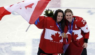 Goalkeeper Shannon Szabados of Canada (1) and Hayley Wickenheiser of Canada (22) celebrate after the medal ceremony in the women's ice hockey tournament at the 2014 Winter Olympics, Friday, Feb. 21, 2014, in Sochi, Russia. Canada won gold after defeated Team USA 3-2 in overtime. (AP Photo/Petr David Josek)