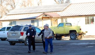 Modoc County Sheriff and Coroner Mike Poindexter, right, walks away from the Cedarville Rancheria tribal headquarters building in Alturas, Calif., on Friday, Feb. 21, 2014. Police say an eviction hearing at the headquarters turned deadly Thursday as a woman who once served as a tribal leader allegedly opened fire, killing four people and critically wounding two others in a gun and knife attack. (AP Photo/Jeff Barnard)