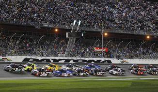 The field takes the green flag to start the NASCAR Truck Series auto race at Daytona International Speedway in Daytona Beach, Fla., Friday, Feb. 21, 2014. (AP Photo/Terry Renna)