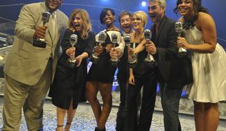 "In a photo provided by Disney, the seven winners of ""American Idol"" gathered for the first time Thursday Feb. 12, 2009  for the grand opening of The American Idol Experience attraction at Walt Disney World Resort in Lake Buena Vista, Fla. From left are Ruben Studdard, Kelly Clarkson, Fantasia Barrino, David Cook, Carrie Underwood, Taylor Hicks and Jordin Sparks  hold silver microphone awards presented to them at the event. (AP Photo/Gene Duncan/Disney)"