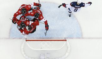 USA forward Zach Parise skates off the ice as Canadian players celebrate after a men's semifinal ice hockey game at the 2014 Winter Olympics, Friday, Feb. 21, 2014, in Sochi, Russia. Canada won 1-0 to advance to the gold medal game. (AP Photo/David J. Phillip )