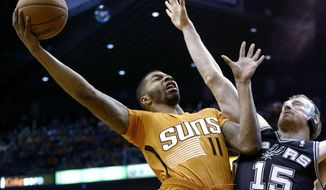 Phoenix Suns' Markieff Morris (11) tries to get off a shot over San Antonio Spurs' Matt Bonner (15) during the first half of an NBA basketball game, Friday, Feb. 21, 2014, in Phoenix. (AP Photo/Ross D. Franklin)