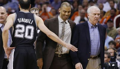 San Antonio Spurs coach Gregg Popovich, right, is escorted back to the bench by assistant coach Ime Udoka, second from right, as they walk past Manu Ginobili (20), of Argentina, who holds out his hand, after Popovich was called for a technical foul during the first half of an NBA basketball game against the Phoenix Suns, Friday, Feb. 21, 2014, in Phoenix. (AP Photo/Ross D. Franklin)