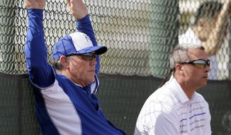 Kansas City Royals manager Ned Yost, left, and Senior Vice President of Baseball Operations and General Manager Dayton Moore, right, watch batting practice during spring training baseball practice, Wednesday, Feb. 19, 2014, in Surprise, Ariz. (AP Photo/Tony Gutierrez)