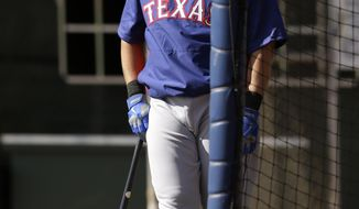 Texas Rangers' Shin-Soo Choo, of South Korea, watches the flight of a ball as he waits his turn in the batting cage during baseball spring training Tuesday, Feb. 18, 2014, in Surprise, Ariz. (AP Photo/Tony Gutierrez)