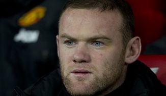 Manchester United's Wayne Rooney sits on the substitutes bench before his team's English Premier League soccer match against Cardiff City at Old Trafford Stadium, Manchester, England, Tuesday Jan. 28, 2014. (AP Photo/Jon Super)