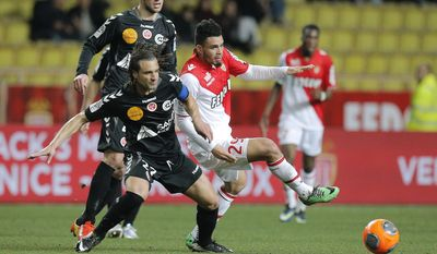 Monaco's Emmanuel Riviere, right, challenges for the ball with Reims' player Mickael Tacalfred during their French League One soccer match, in Monaco stadium, Friday, Feb. 21 , 2014. (AP Photo/Lionel Cironneau)