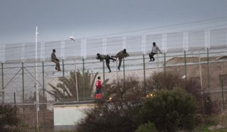 Sub-Saharan migrants climb over a metallic fence that divides Morocco and the Spanish enclave of Melilla, as a Red Cross worker is on-hand to offer humanitarian assistance, Monday Feb. 17, 2014. A Spanish official says about 200 sub-Saharan migrants stormed a barbed-wire border fence along Spain's northwest African enclave of Melilla, with about 50 of them making it over. A spokesman for the Interior Ministry's office in Melilla said the melee began early Monday. The Spanish city of Melilla lies on the African continent, surrounded by Morocco and the Mediterranean Sea. Migrants hoping to get to Europe camp on the Moroccan side, with several thousand trying each year to enter the city and Spain's other coastal enclave of Ceuta. (AP Photo/ Jesus Blasco de Avellaneda)