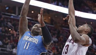 Orlando Magic's Glen Davis (11) shoots over Cleveland Cavaliers' Tristan Thompson (13) during the first quarter of an NBA basketball game Wednesday, Feb. 19, 2014, in Cleveland. (AP Photo/Tony Dejak)