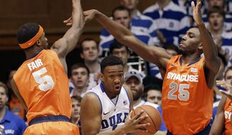 Duke's Jabari Parker is pressured by Syracuse's C.J. Fair (5) and Rakeem Christmas (25) during the first half of an NCAA college basketball game in Durham, N.C., Saturday, Feb. 22, 2014. (AP Photo/Gerry Broome)