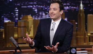 """FILE- In this Feb. 18, 2014 file photo released by NBC, host Jimmy Fallon is seated at his desk during """"The Tonight Show Starring Jimmy Fallon,"""" in New York. Fallon, a New Yorker who wanted the excitement of the nation's largest city to permeate his show, brought """"The Tonight Show"""" back to New York after 40 years on the West Coast. Producing the show in New York also nets NBC a 30 percent tax credit that can save the network more than $20 million a year. (AP Photo/NBC, Lloyd Bishop, File)"""