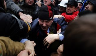 A suspected supporter of Ukraine's embattled president Viktor Yanukovych, center, is assaulted by anti-government protesters in Kiev, Ukraine, Saturday, Feb. 22, 2014. Fears that Ukraine could split in two mounted Saturday as regional lawmakers in the pro-Russian east questioned the authority of the national parliament. Protesters took control of Ukraine's capital and parliament sought to oust the president. (AP Photo/ Marko Drobnjakovic)