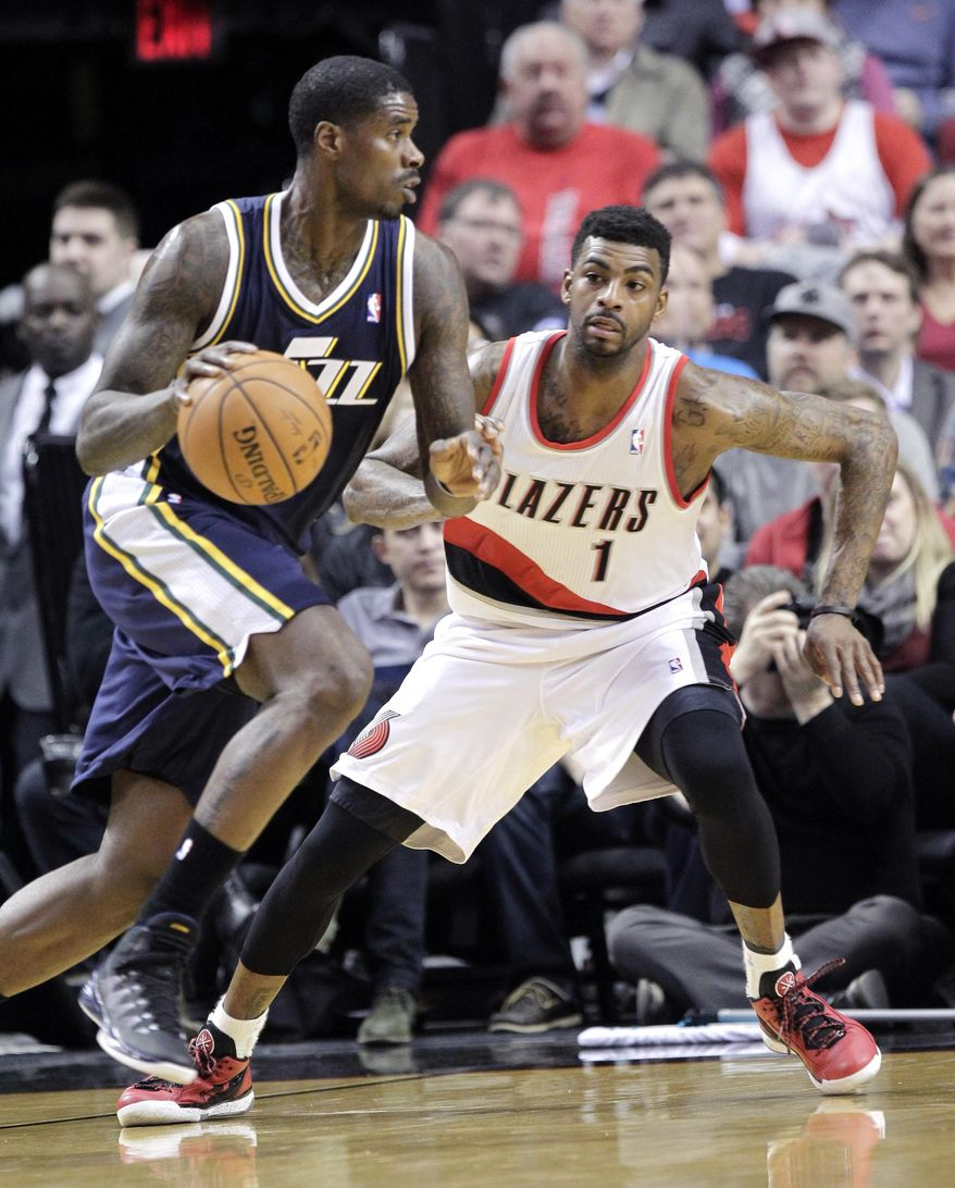 Utah Jazz forward Marvin Williams, left, drives on Portland Trail Blazers forward Dorell Wright during the first half of an NBA basketball game in Portland, Ore., Friday, Feb. 21, 2014. (AP Photo/Don Ryan)