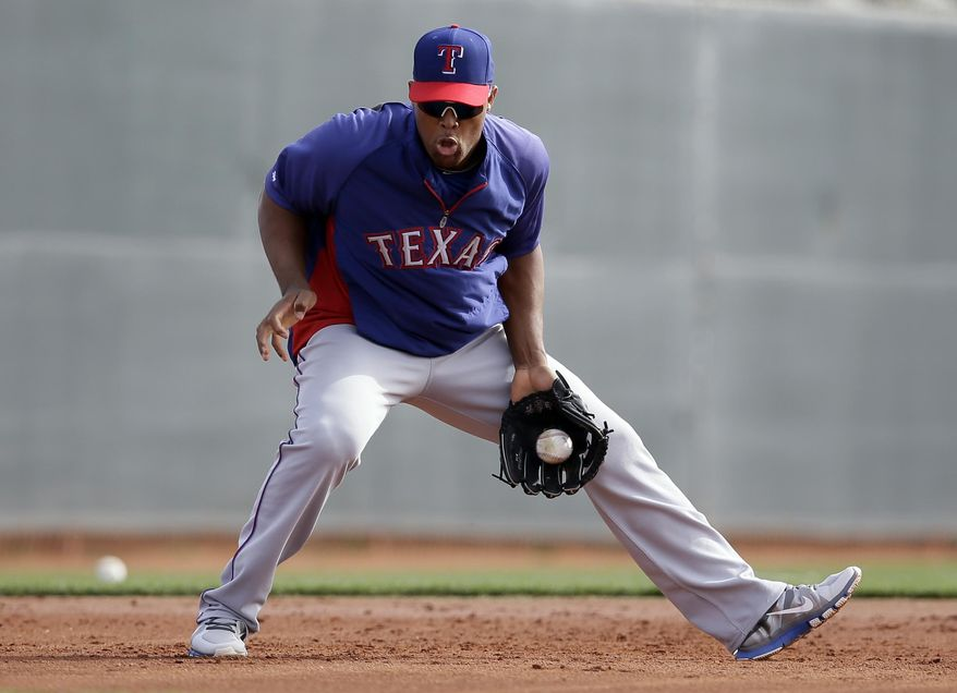 Texas Rangers' Adrian Beltre fields a ground ball during baseball spring training, Wednesday, Feb. 19, 2014, in Surprise, Ariz. (AP Photo/Tony Gutierrez)