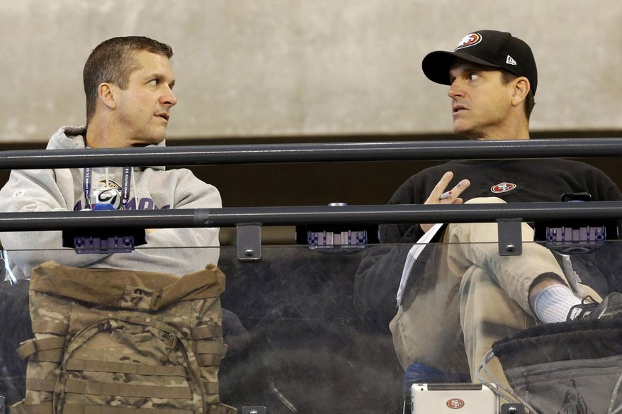 San Francisco 49ers head coach Jim Harbaugh, right, talks with Baltimore Ravens head coach John Harbaugh at the NFL football scouting combine in Indianapolis, Saturday, Feb. 22, 2014. (AP Photo/Nam Y. Huh)