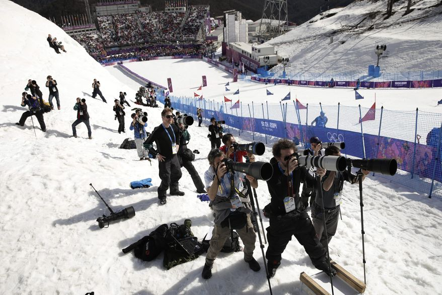 Photographers take pictures during the men's and women's snowboard parallel slalom quarterfinals at the Rosa Khutor Extreme Park, at the 2014 Winter Olympics, Saturday, Feb. 22, 2014, in Krasnaya Polyana, Russia. (AP Photo/Jae C. Hong)