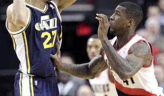 Utah Jazz center Rudy Gobert, left, maneuvers against Portland Trail Blazers forward Thomas Robinson during the first half of an NBA basketball game in Portland, Ore., Friday, Feb. 21, 2014. (AP Photo/Don Ryan)