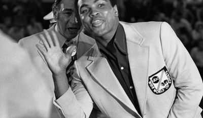 FILE - In this Aug. 7, 1972 file photo, Muhammad Ali, former world heavyweight boxing champion, jokes with television sports commentator Howard Cosell, speaking behind him, before the start of the Olympic boxing trials in West Point, NY. Ali joined Cosell as a commentator at the boxing finals. (AP Photo)