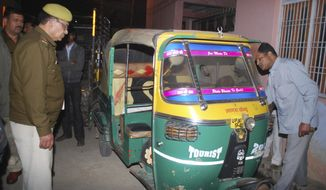 In this Thursday, Feb. 20, 2014 photo, Indian policemen investigate an auto rickshaw of  Bunty Sharma, 32, outside his house, in Agra, India. Bunty fatally stabbed his American wife Erin W. Willinger before killing himself in Agra, the city that is home to the Taj Mahal and where the couple married in October, police said Saturday. Willinger's body was found with multiple stab wounds late Thursday night in a deserted part of the city, said Agra police chief Shalabh Mathur. Her husband Bunty Sharma committed suicide by igniting cooking gas and causing a massive explosion in his home, Mathur said. (AP Photo)