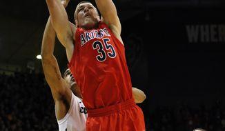 Arizona's Kaleb Tarczewski grabs a rebound during the first half of an NCAA college basketball game against Colorado, in Boulder, Colo., Saturday, Feb. 22, 2014. (AP Photo/Brennan Linsley)