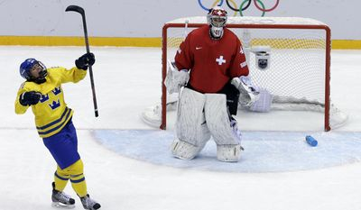Erica Uden Johansson of Sweden (21)reacts after scoring a goal on goalkeeper Florence Schelling of Switzerland (41) during the women's bronze medal ice hockey game at the 2014 Winter Olympics, Thursday, Feb. 20, 2014, in Sochi, Russia. (AP Photo/David J. Phillip )