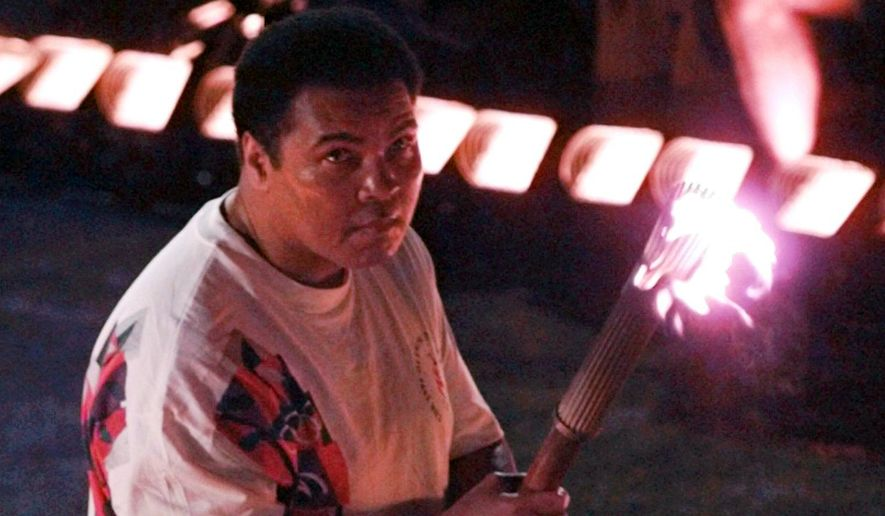 FILE - In this Friday, July 19, 1996 file photo, Muhammad Ali holds a torch as he watches as the flame climb up to the Olympic cauldron during the opening ceremonies of the Summer Olympics in Atlanta. As Cassius Clay, he won the gold medal as a light heavyweight at the 1960 Rome Olympics. (AP Photo/Doug Mills)