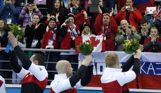 E.J. Harnden, left, Ryan Fry, center, and Brad Jacobs, acknowledge the fans during the flower ceremony after defeating Britain in the men's curling gold medal game  at the 2014 Winter Olympics, Friday, Feb. 21, 2014, in Sochi, Russia. (AP Photo/Robert F. Bukaty)