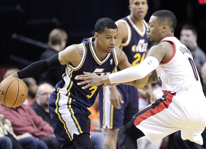 Utah Jazz guard Trey Burke, left, drives on Portland Trail Blazers guard Damian Lillard during the first half of an NBA basketball game in Portland, Ore., Friday, Feb. 21, 2014. (AP Photo/Don Ryan)