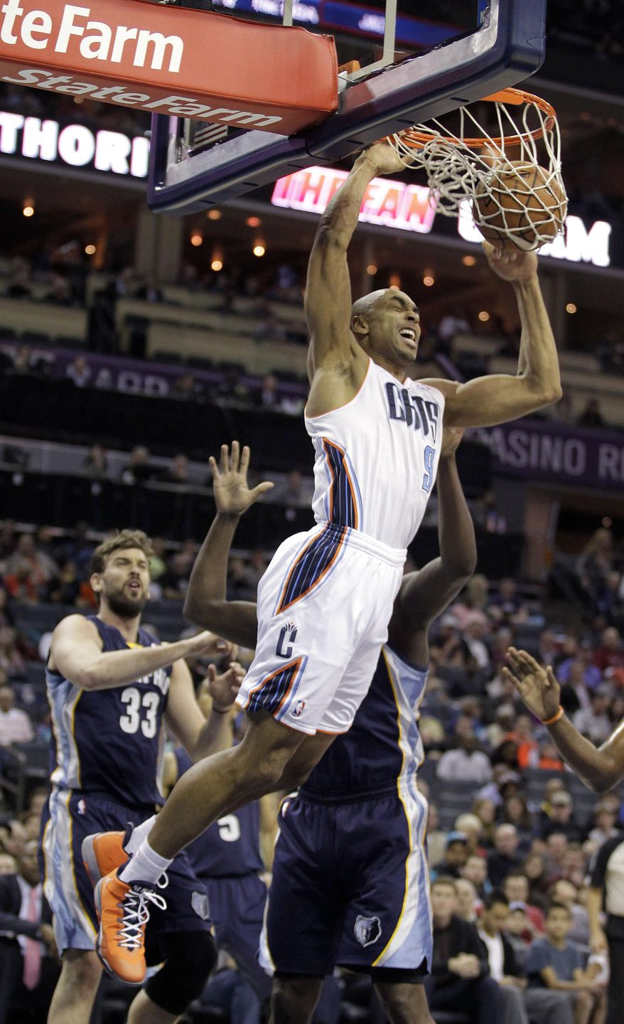 The Charlotte Bobcats' Gerald Henderson (9) dunks over the Memphis Grizzlies' Marc Gasol (33) and Zach Randolph during the first half of an NBA basketball game in Charlotte, N.C., Saturday, Feb. 22, 2014. (AP Photo/Bob Leverone)