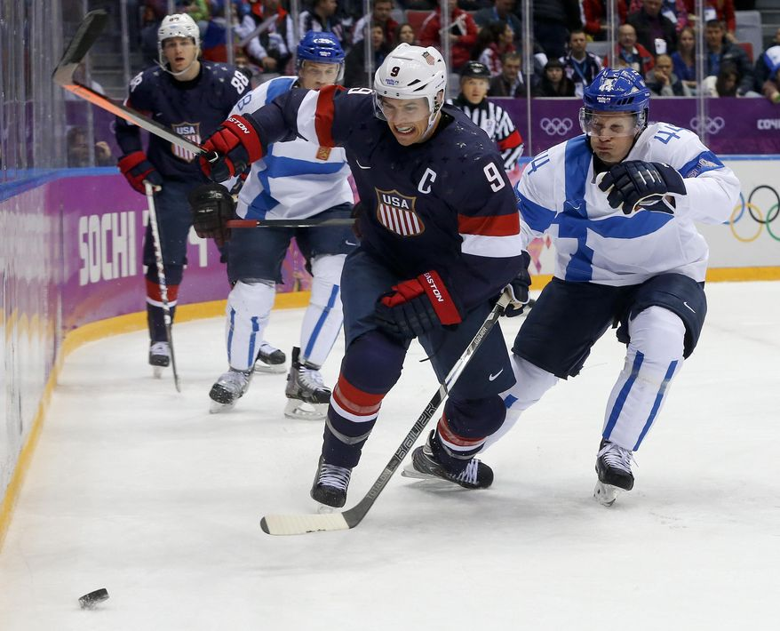 USA forward Zach Parise and Finland defenseman Kimmo Timonen vie for the puck during the first period of the men's bronze medal ice hockey game at the 2014 Winter Olympics, Saturday, Feb. 22, 2014, in Sochi, Russia. (AP Photo/Mark Humphrey)