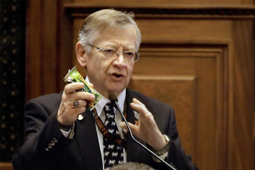 """In this Feb. 20, 2014 photo, Illinois state Rep. Donald Moffitt, R-Galesburg, holds up an example of a healthy snack on the House floor encouraging fellow lawmakers, lobbyists or anyone else who wants to shed some pounds and eat healthier to sign up for the """"fitness caucus"""" at the state Capitol in Springfield, Ill. The caucus will kick off with a weight-loss competition and run through this year's legislative session. Moffitt began an exercise routine two years ago when his doctor said he'd need to lose 10 pounds or take diabetes medication. Since then, he lost 100 pounds and walks five miles a day. (AP Photo/Seth Perlman)"""