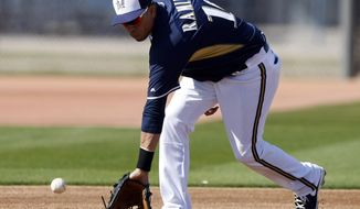 Milwaukee Brewers third baseman Aramis Ramirez fields grounders during a spring training baseball practice, Saturday, Feb. 22, 2014, in Phoenix. (AP Photo/Rick Scuteri)