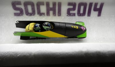 The team from Jamaica JAM-1, piloted by Winston Watts and brakeman Marvin Dixon, take a curve during the men's two-man bobsled competition at the 2014 Winter Olympics, Sunday, Feb. 16, 2014, in Krasnaya Polyana, Russia. (AP Photo/Natacha Pisarenko)