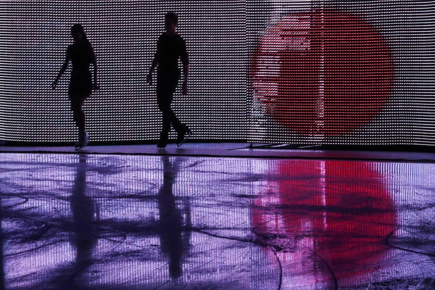 Elena Ilinykh and Nikita Katsalapov of Russia are silhouetted by a display of the Japanese flag before they perform in the figure skating exhibition gala at the Iceberg Skating Palace during the 2014 Winter Olympics, Saturday, Feb. 22, 2014, in Sochi, Russia. (AP Photo/Ivan Sekretarev)