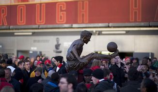 Fans gather around the statue of former Arsenal player Dennis Bergkamp, in front of the Emirates Stadium, in London, Saturday, Feb. 22, 2014. (AP Photo/Bogdan Maran)
