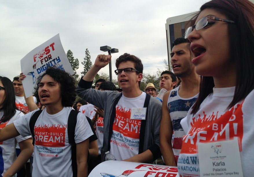 "Youth from United We Dream chant slogans calling for an end to deportations outside the Immigration and Customs Enforcement (ICE) offices in downtown Phoenix. Top Hispanic leaders asked President Obama last week to grant some illegal immigrants access to Obamacare, saying the ""dreamers"" to whom the White House has given tentative work permits are already paying taxes, so they deserve government benefits. (Associated Press)"