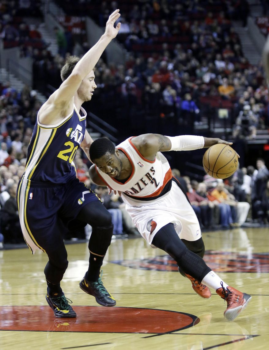 Portland Trail Blazers guard Wesley Matthews, right, drives on Utah Jazz guard Gordon Hayward during the first half of an NBA basketball game in Portland, Ore., Friday, Feb. 21, 2014. (AP Photo/Don Ryan)