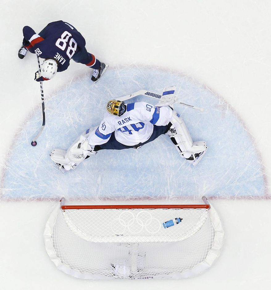 Finland goaltender Tuukka Rask blocks a shot by USA forward Patrick Kane during the first period of the men's bronze medal ice hockey game at the 2014 Winter Olympics, Saturday, Feb. 22, 2014, in Sochi, Russia. (AP Photo/David J. Phillip )