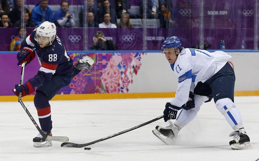 USA forward Patrick Kane breaks his stick while taking a shot on goal as Finland forward Leo Komarov defends during the second period of the men's bronze medal ice hockey game at the 2014 Winter Olympics, Saturday, Feb. 22, 2014, in Sochi, Russia. Komarov was called for slashing on the play and the USA was awarded a penalty shot. (AP Photo/Petr David Josek)