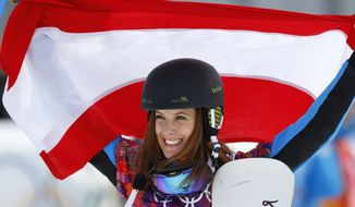 Women's snowboard parallel slalom gold medalist Julia Dujmovits of Austria celebrates during a flower ceremony at the Rosa Khutor Extreme Park, at the 2014 Winter Olympics, Saturday, Feb. 22, 2014, in Krasnaya Polyana, Russia.  (AP Photo/Sergei Grits)
